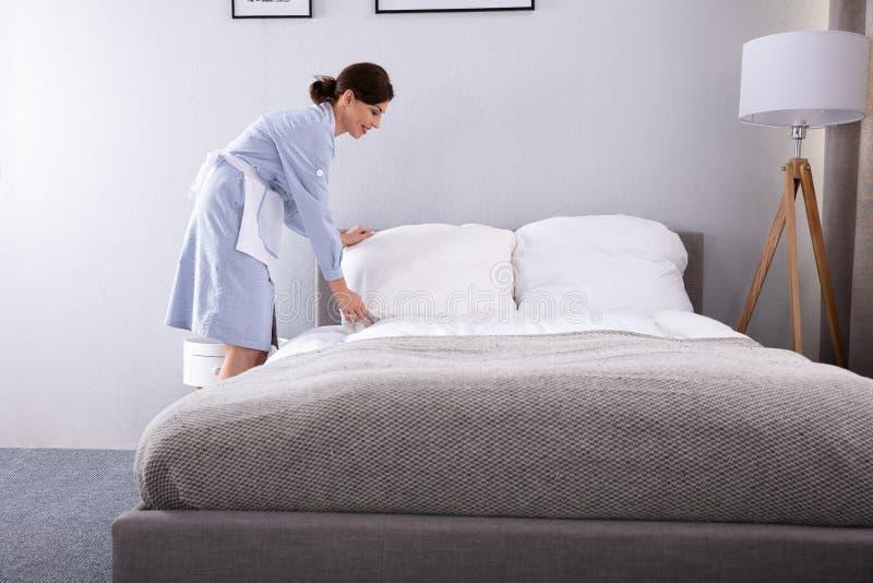 Empregada que faz a cama na sala de hotel foto de stock
