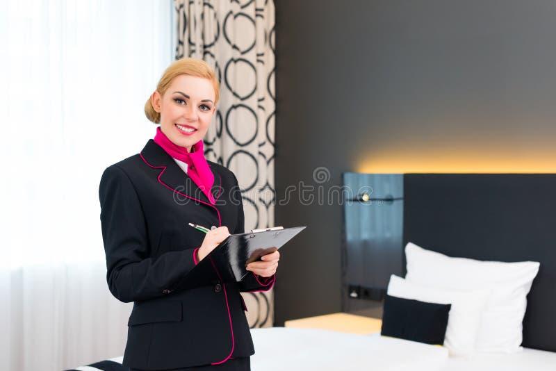 Empregada que verifica a sala de hotel imagem de stock royalty free