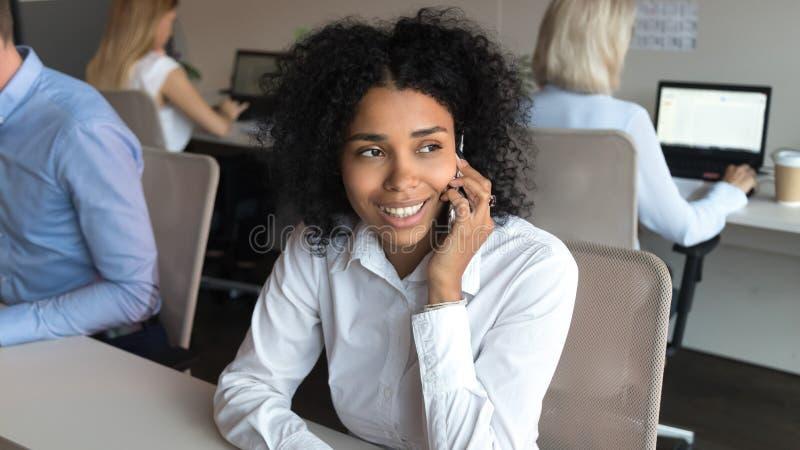 Empregado afro-americano de sorriso que fala no telefone que senta-se no escritório fotografia de stock royalty free