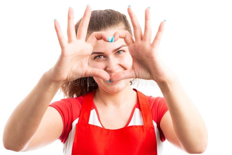 Empregado alegre do supermercado da mulher que faz o sinal do coração com mãos fotografia de stock