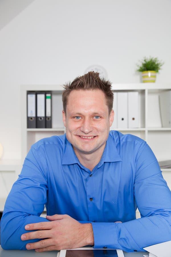 Empregado bem sucedido novo que senta-se em sua mesa fotos de stock royalty free