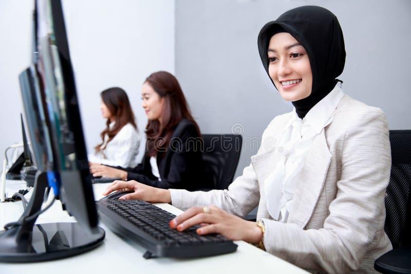 Empregado bonito que sorri ao trabalhar no escritório imagens de stock