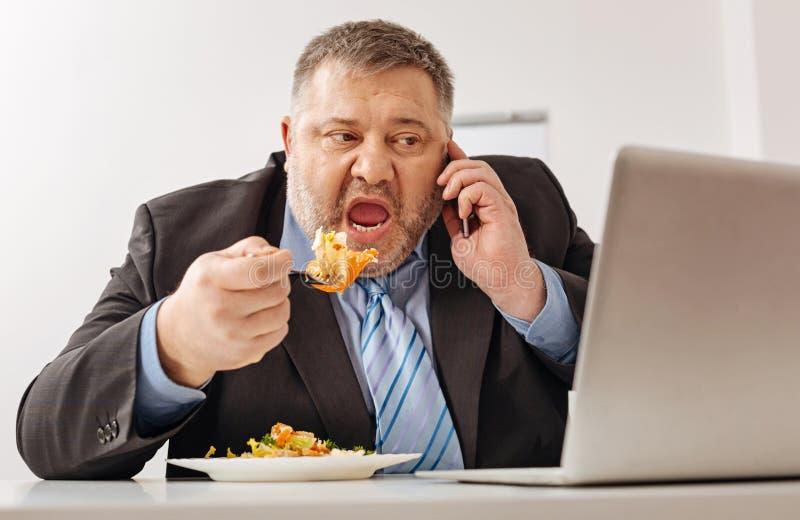 Empregado cansado com fome da empresa sobrecarregado com o trabalho foto de stock royalty free