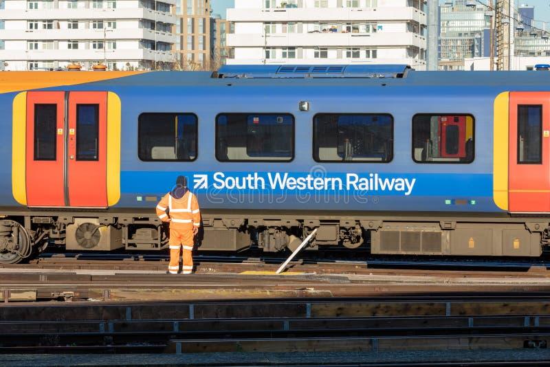Empregado da estrada de ferro na frente de trem movente foto de stock