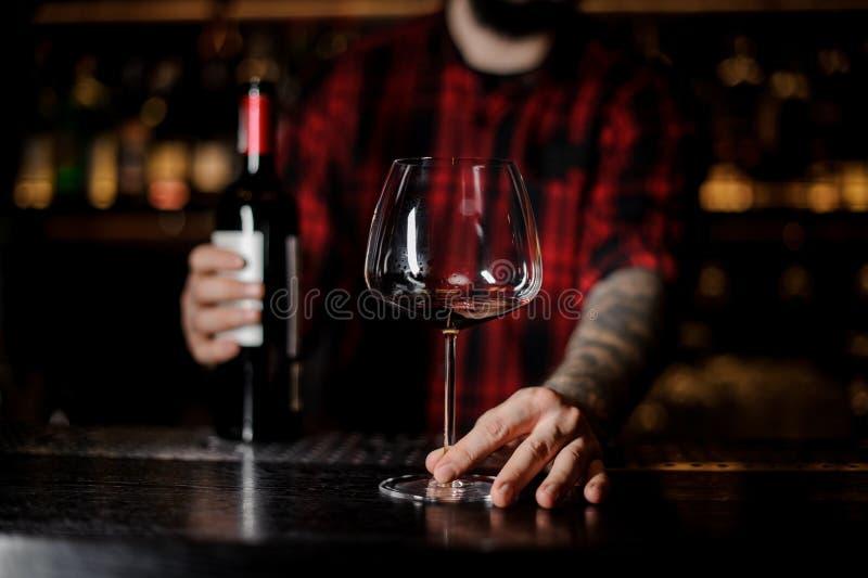 Empregado de bar com um vidro vazio do burgunya e uma garrafa do vinho tinto fotos de stock
