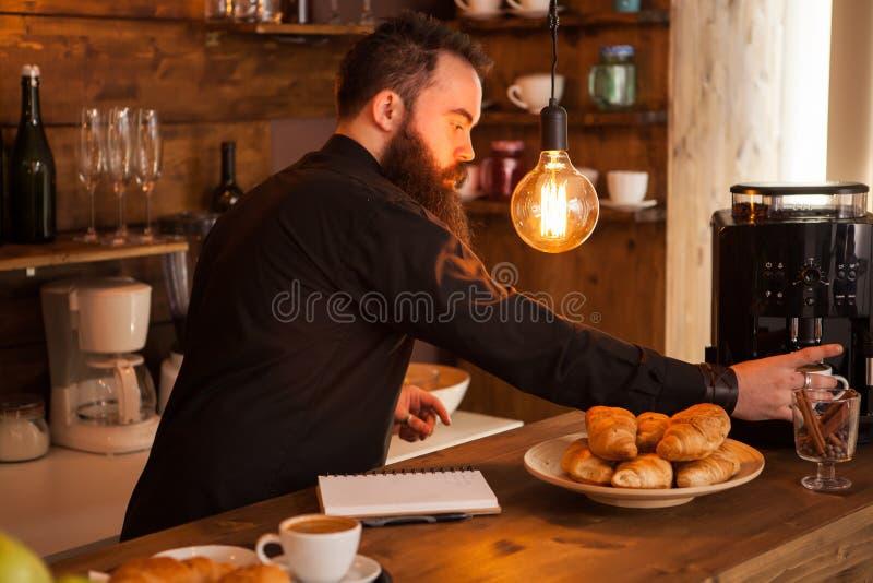 Empregado de bar consider?vel atr?s de uma barra com um caf? preparado fotografia de stock royalty free