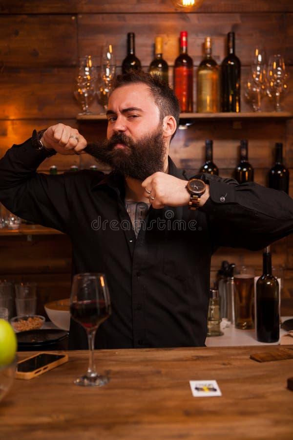 Empregado de bar farpado que é engraçado com sua barba fotografia de stock royalty free