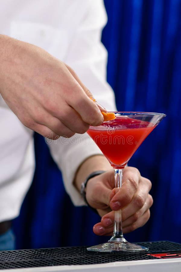 Empregado de bar não identificado que prepara o fundo do azul do cocktai imagem de stock royalty free