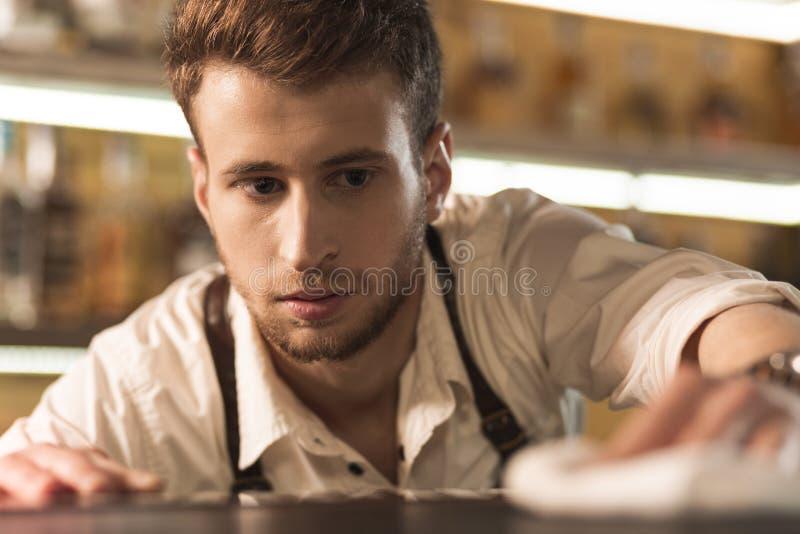 Empregado de bar novo agradável que verifica a limpeza do contador da barra imagens de stock