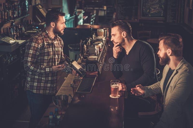 Empregado de bar polido que mostra uma garrafa de uísque aos clientes no contador da barra no bar foto de stock
