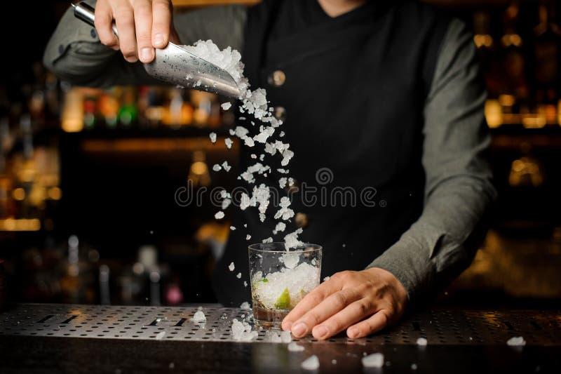 Empregado de bar que adiciona cubos de gelo no vidro de cocktail Processo de maki foto de stock royalty free