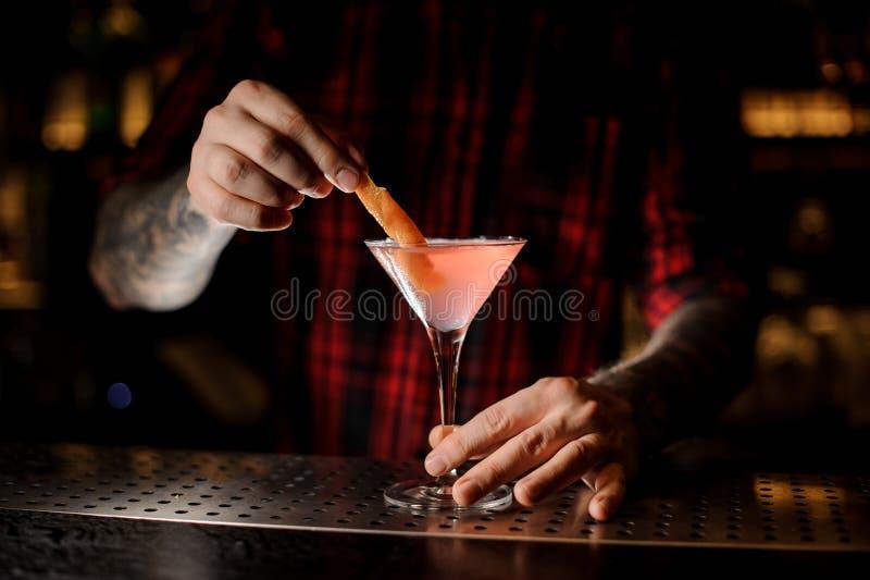 Empregado de bar que decora o cocktail cosmopolita com uma casca alaranjada imagens de stock royalty free