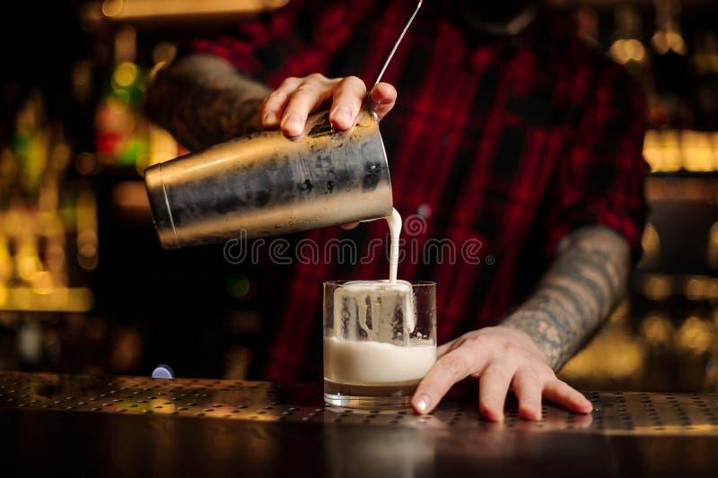 Empregado de bar que derrama a bebida alcoólica cremosa grossa fresca em um vidro imagem de stock royalty free