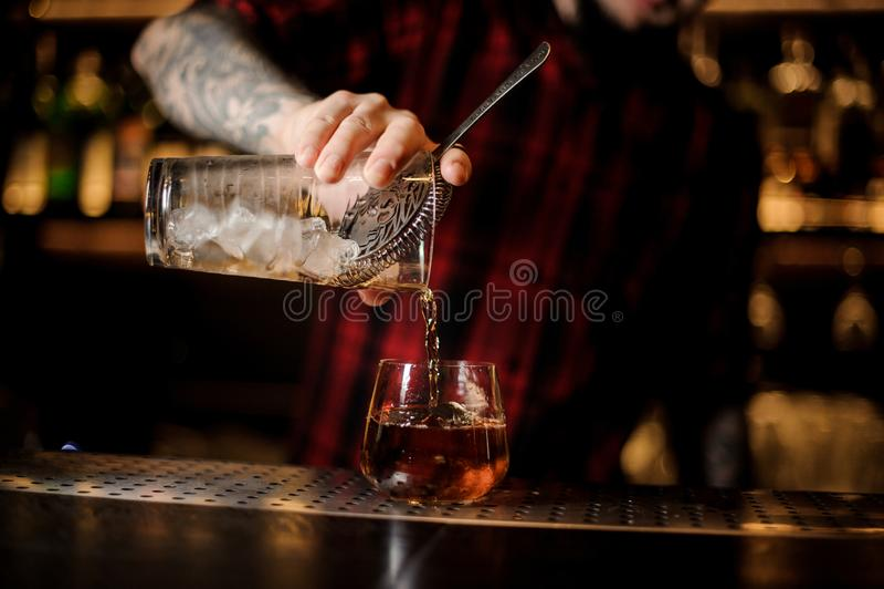 Empregado de bar que derrama a bebida fresca em um vidro do dof do uísque foto de stock royalty free