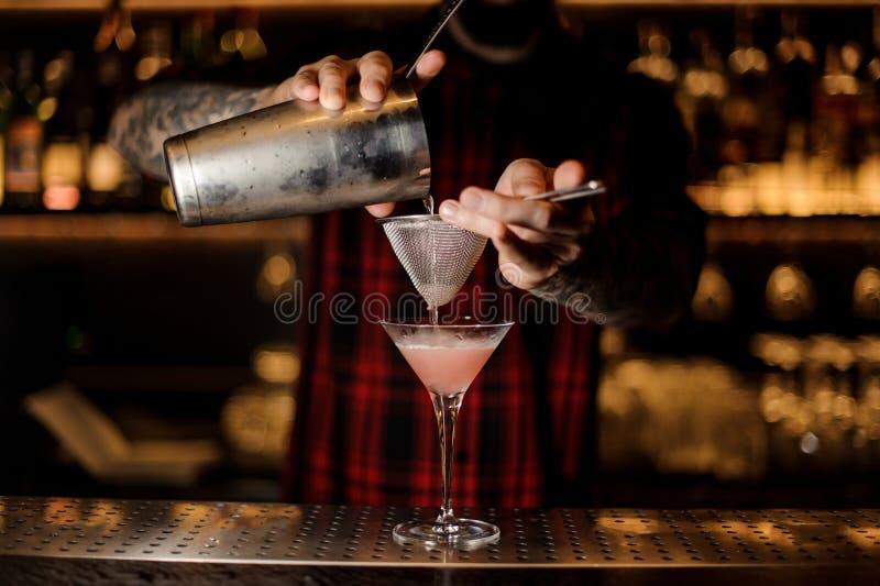 Empregado de bar que derrama o cocktail cosmopolita em um vidro imagem de stock royalty free