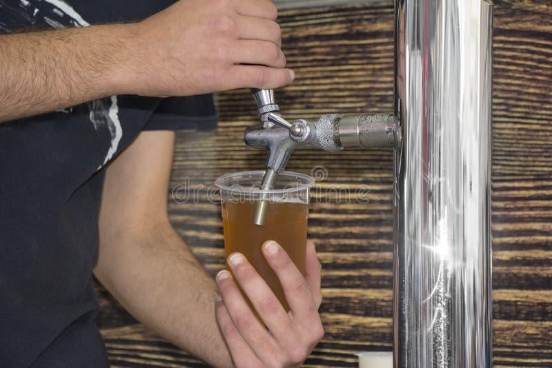 Empregado de bar que enchem o vidro plástico com a cerveja imagem de stock royalty free