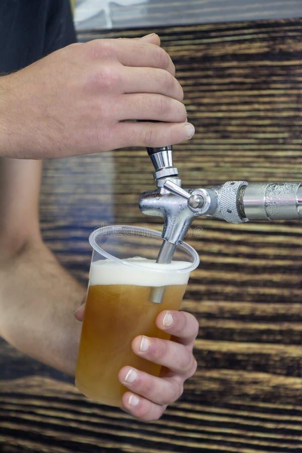 Empregado de bar que enchem o vidro plástico com a cerveja imagens de stock