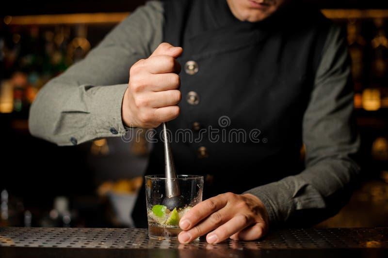 Empregado de bar que espreme o suco do cal fresco usando a imprensa do citrino imagem de stock