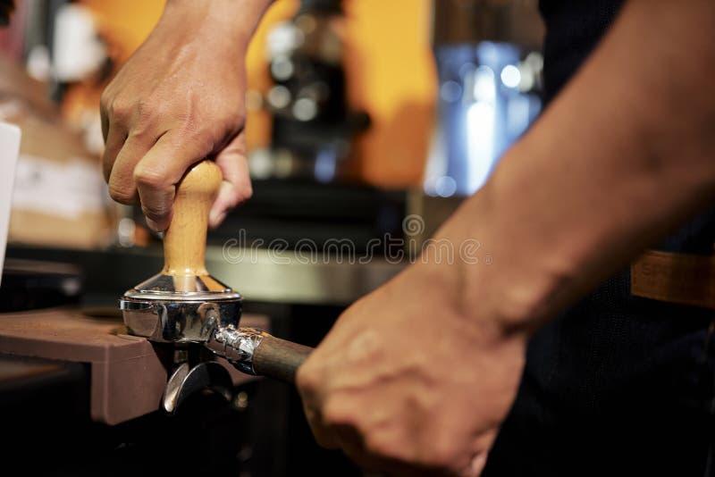 Empregado de bar que moem feij?es de caf? imagens de stock royalty free