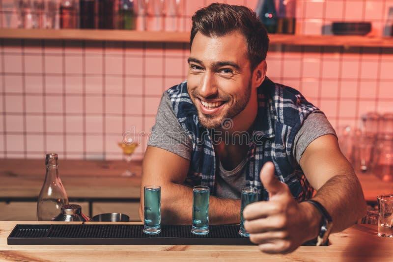 Empregado de bar que mostra o polegar acima no contador imagem de stock