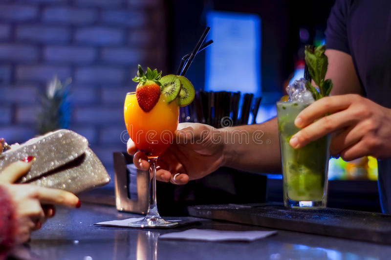 Empregado de bar que servem cocktail quando a mulher esperar para pagar fotos de stock