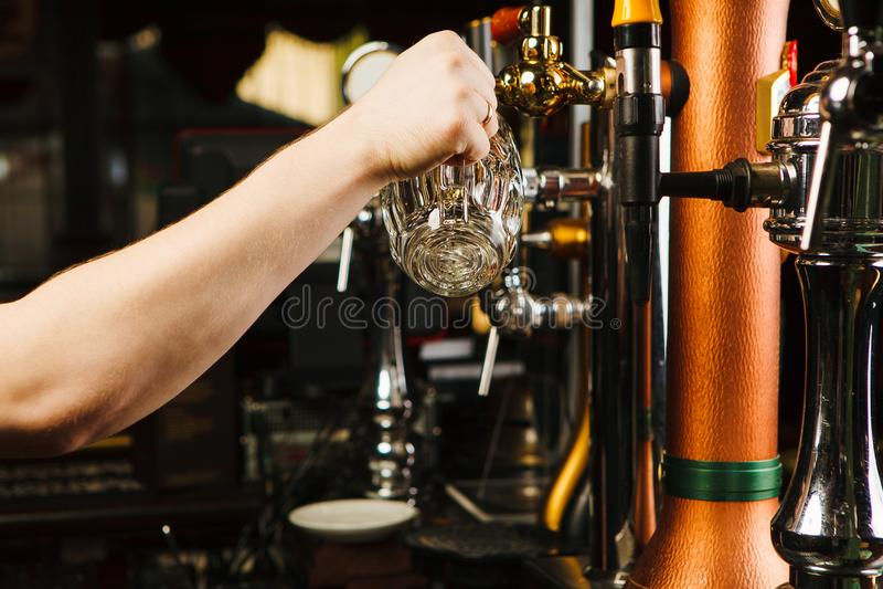 Empregado de bar que vai derramar a cerveja no cálice de vidro da torneira fotografia de stock