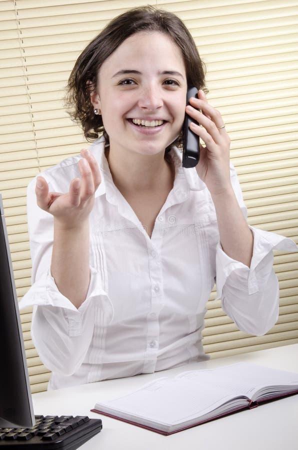 Empregado de escritório durante uma conversa telefónica foto de stock royalty free