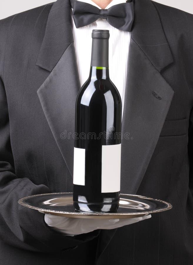 Empregado de mesa com etiqueta do espaço em branco do frasco de vinho vermelho imagens de stock