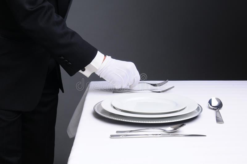Empregado de mesa que ajusta a tabela de jantar formal imagem de stock