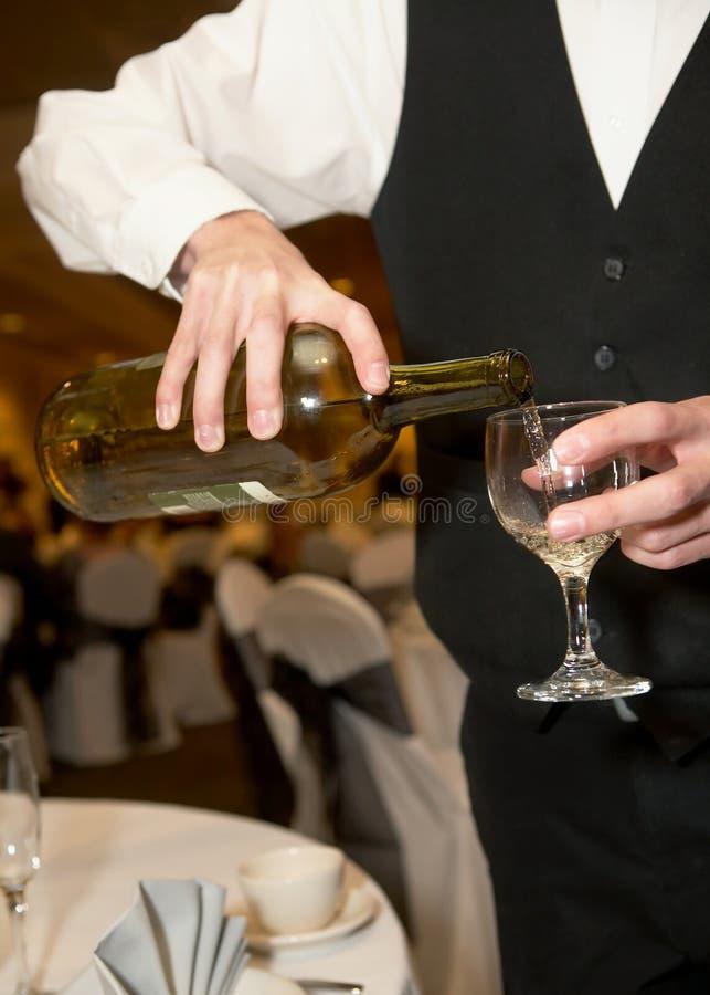 Empregado de mesa que derrama Champagne foto de stock royalty free