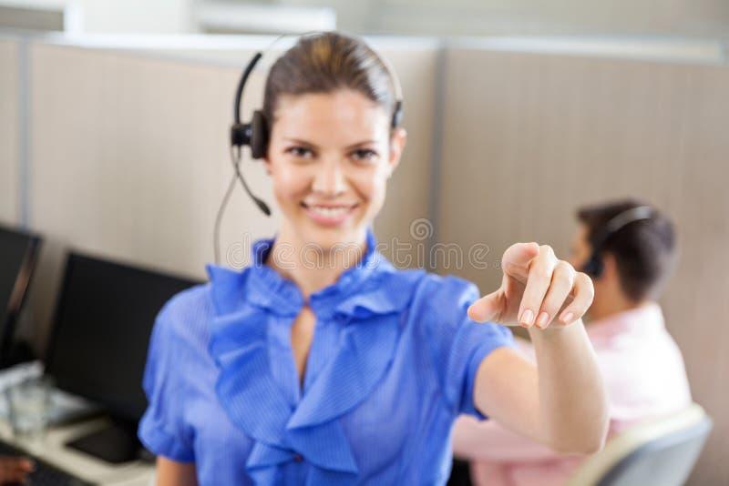 Empregado de sorriso do centro de atendimento que aponta no escritório fotos de stock royalty free