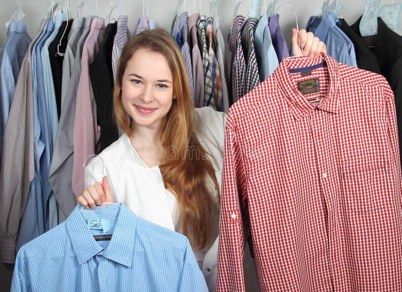 Empregado de uma tinturaria que apresenta duas camisas limpas foto de stock royalty free