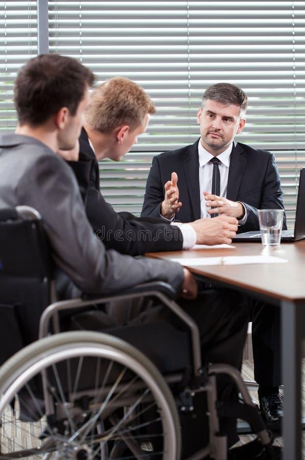 Empregado deficiente ao lado da tabela de conferência imagem de stock royalty free