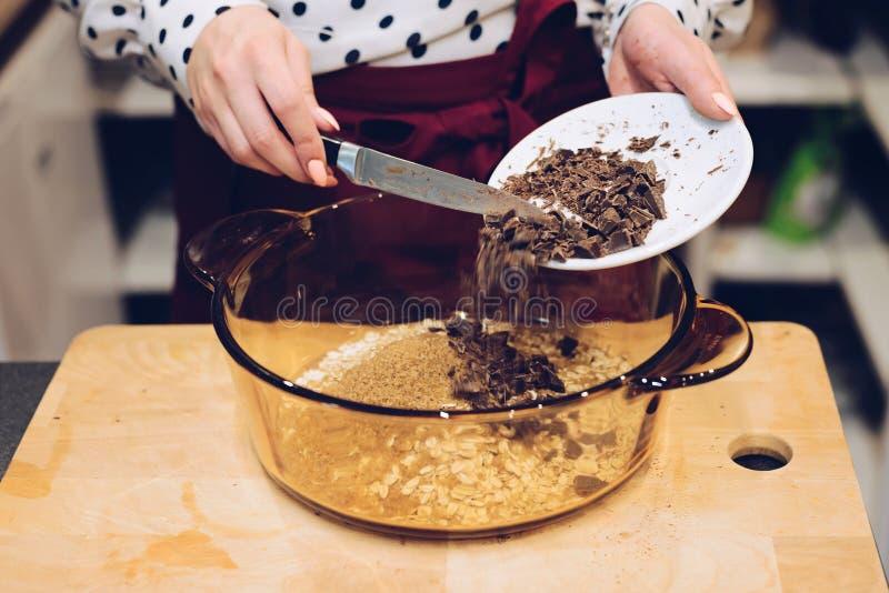 Empregado do café que adiciona partes de chocolate à bacia imagem de stock