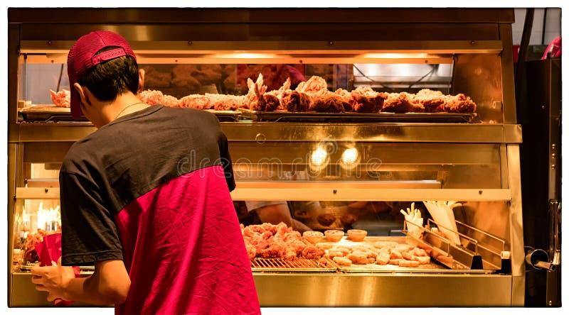 Empregado do salário mínimo em uma cozinha do restaurante do fast food foto de stock royalty free