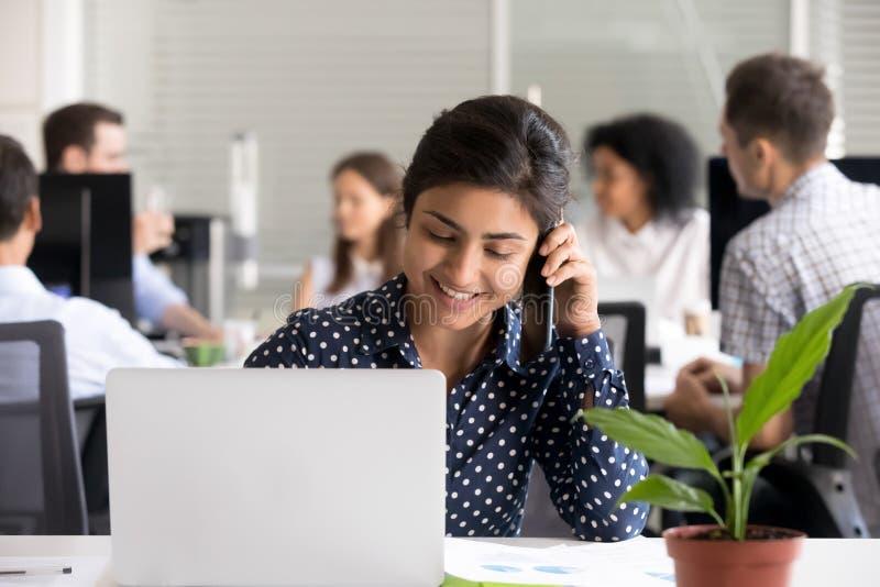 Empregado do sexo feminino indiano de sorriso que fala no telefone foto de stock royalty free