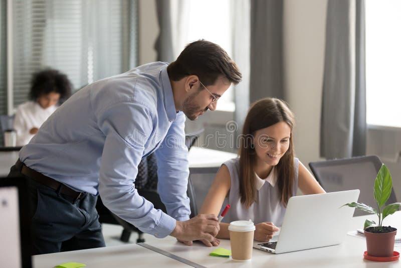 Empregado do sexo feminino novo de explicação da tarefa do mentor amigável imagens de stock royalty free