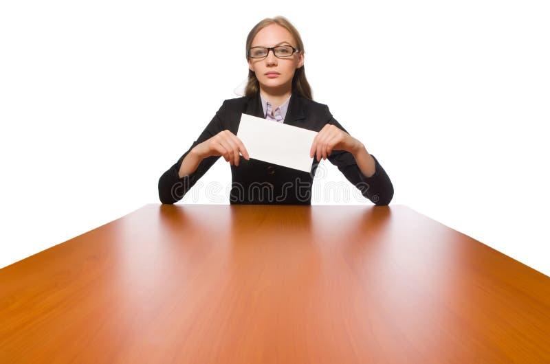 Empregado do sexo feminino que senta-se na tabela longa isolada no branco imagens de stock