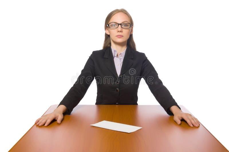 Empregado do sexo feminino que senta-se na tabela longa isolada no branco foto de stock royalty free