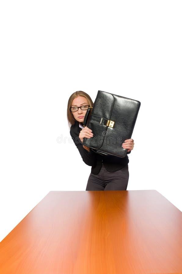Empregado do sexo feminino que senta-se na tabela longa isolada no branco foto de stock