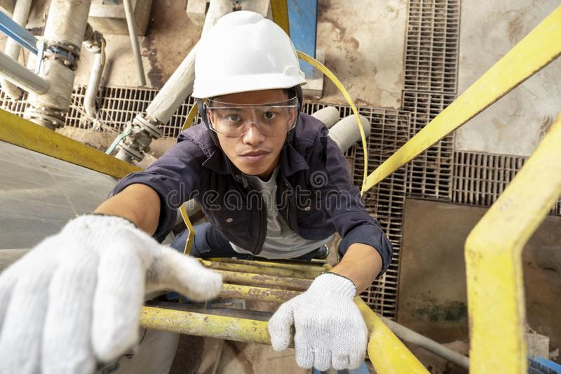 Empregado do sexo masculino asi?tico que veste um capacete de seguran?a que escala a escada imagem de stock royalty free