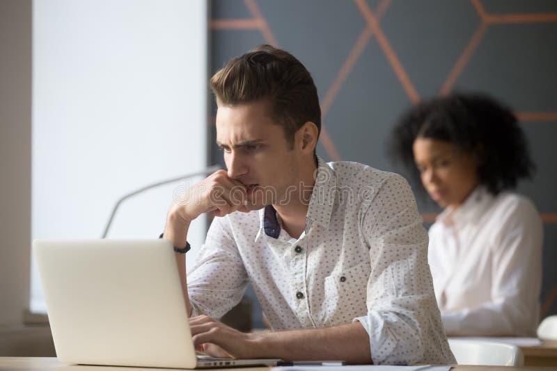 Empregado do sexo masculino sério confundido que resolve o problema em linha do portátil no fotos de stock