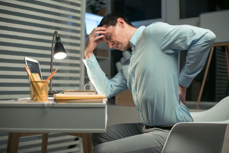 Empregado do sexo masculino triste esgotado pelo trabalho imagem de stock royalty free