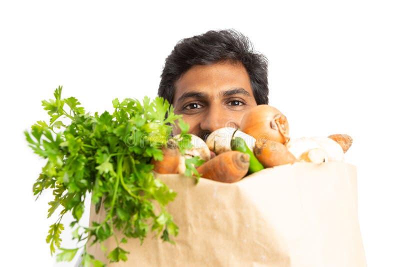 Empregado do supermercado que esconde atrás do saco de mantimento fotos de stock