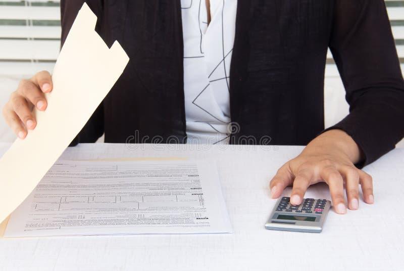 Empregado incorporado que trabalha em dados financeiros no local de trabalho foto de stock