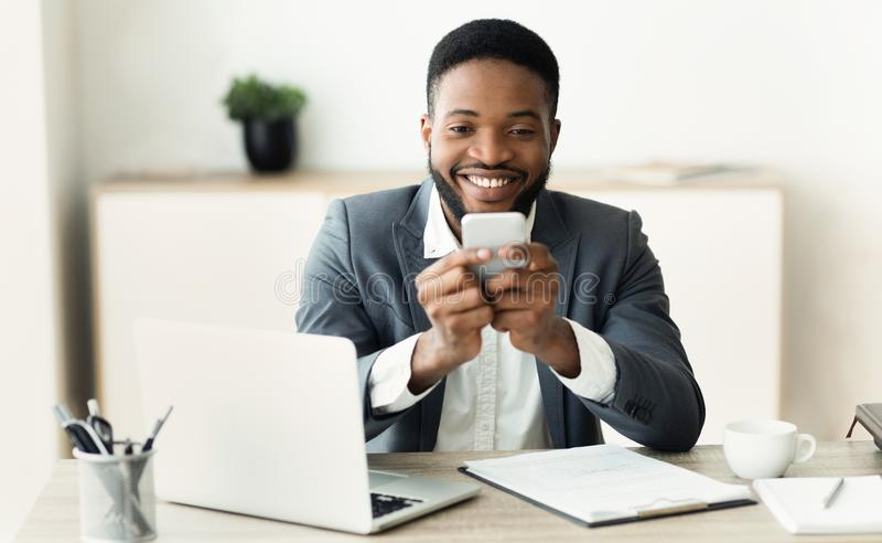 Empregado milenar feliz que olha a tela do smartphone que lê a mensagem agradável fotografia de stock royalty free