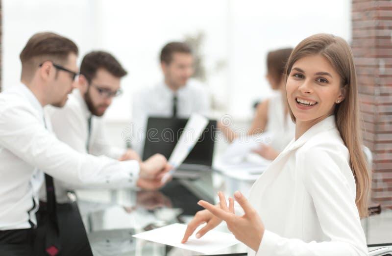 Empregado novo que senta-se em sua mesa e que olha a câmera imagem de stock royalty free