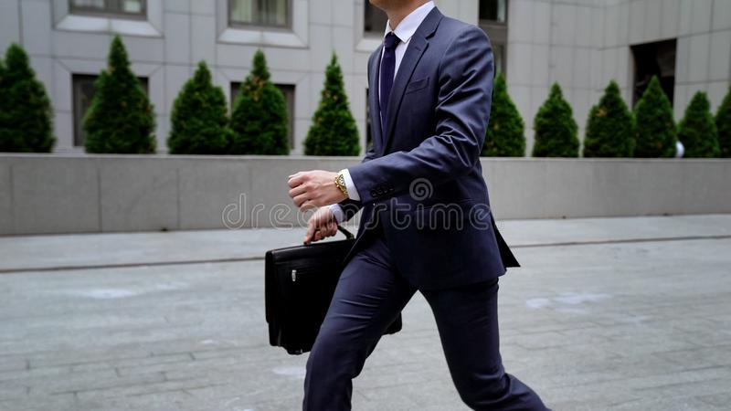 Empregado que apressa-se ao trabalho, correndo ao prédio de escritórios, gestão de tempo, horas de ponta imagens de stock royalty free