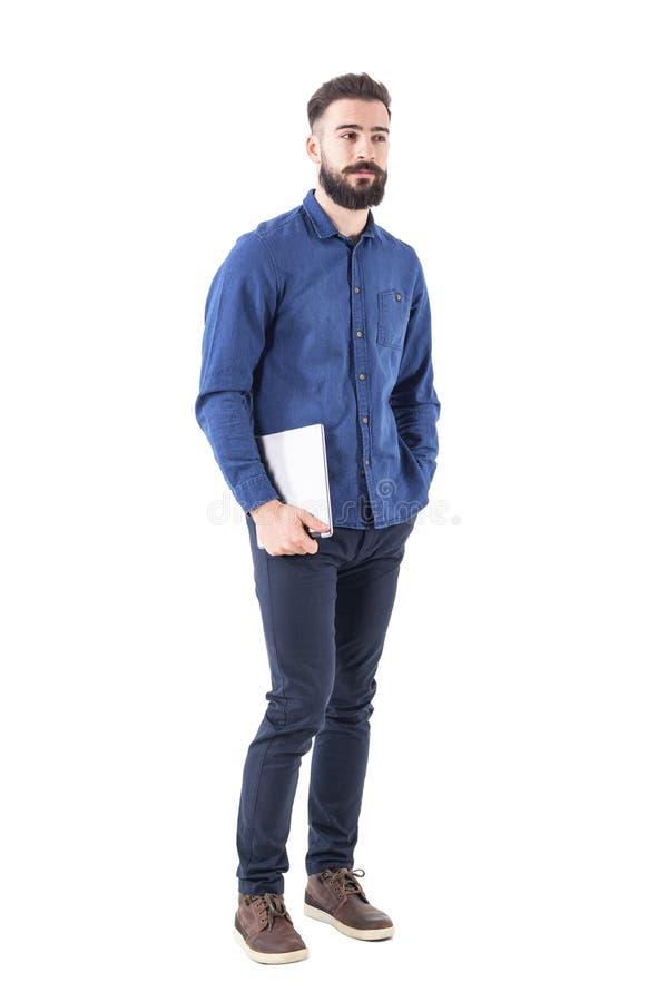 Empregador bem sucedido novo relaxado do negócio que guarda o computador da almofada da tabuleta sob o braço que olha afastado imagens de stock