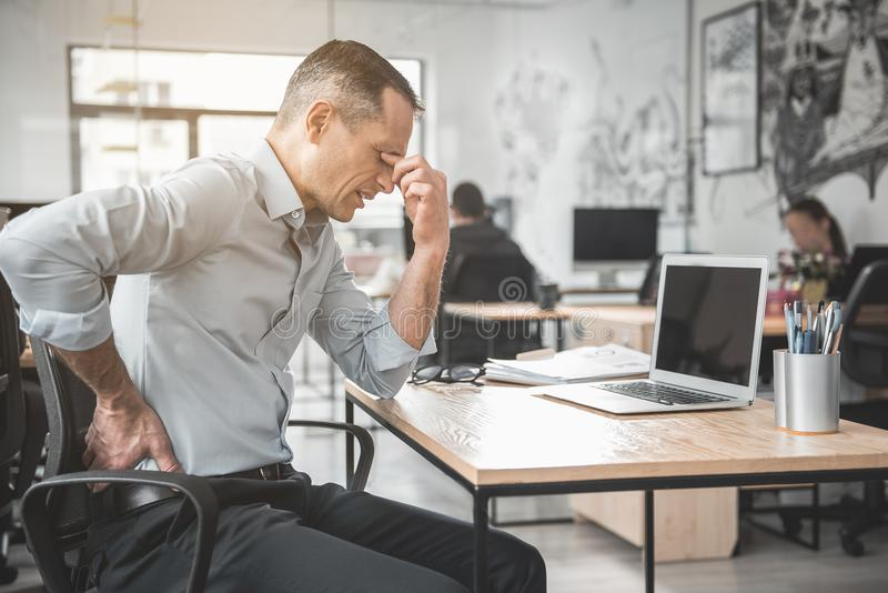 Empregador cansado infeliz no trabalho foto de stock
